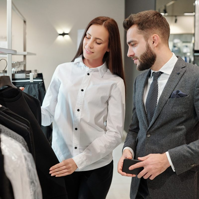 Brunette fashion consultant in white blouse showing sweater to man while giving him advice in clothing store