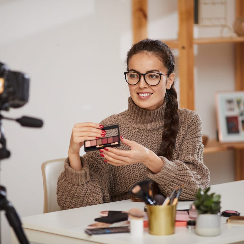 Portrait of smiling young woman showing make up products to camera while filming video review for beauty and lifestyle channel, copy space